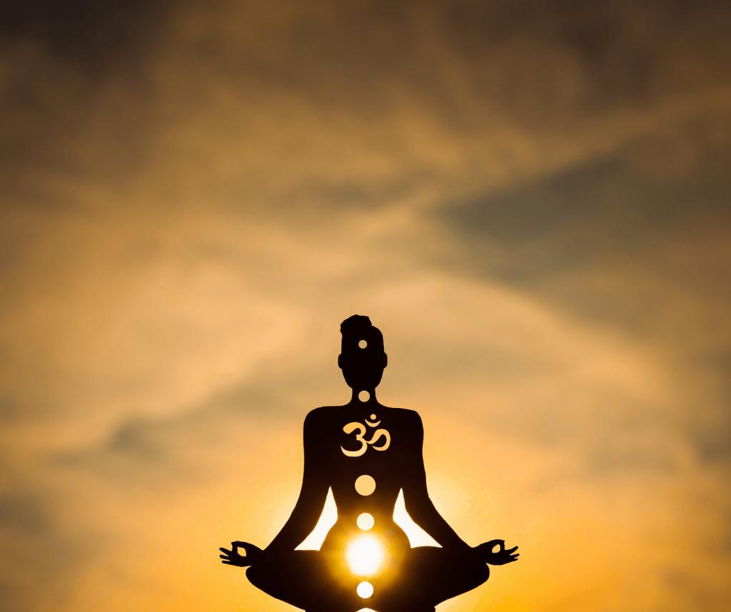 silhouette d'une femme méditant au coucher du soleil