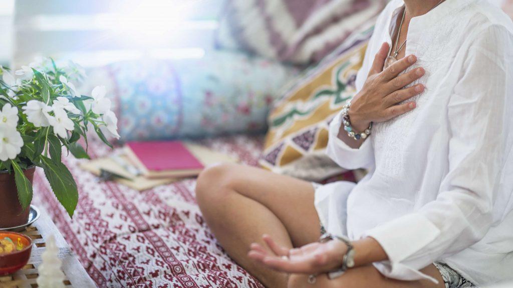 une dame méditant et touchant son chakra du cœur